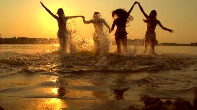 stock-footage-group-of-happy-girls-running-and-playing-in-water-at-the-beach-on-sunset-beauty-and-joyful